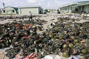 A Georgian soldier in civilian clothes walks past cluttered military equipment in Senaki Military Base